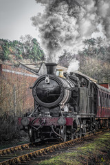 A upright vertical view of a steam train locomotive in motion facing forward and smoking