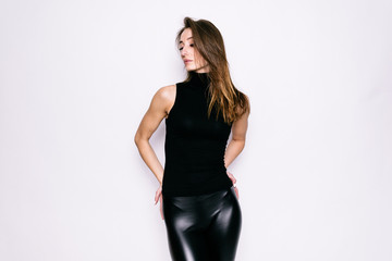 Beautiful young girl in black golf and leather pants on a white background
