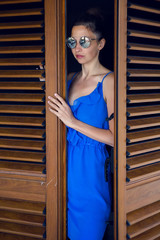 girl in the blue dress stands in the doorway