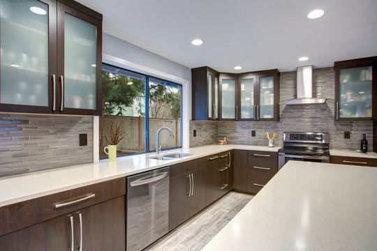 Updated contemporary kitchen room interior in white and dark tones.