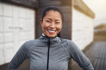 Smiling young Asian woman standing outside before a jog Fotoväggar
