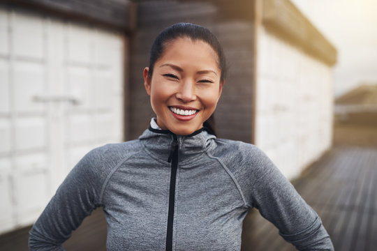 Smiling young Asian woman standing outside before a jog
