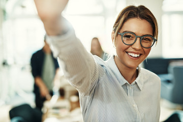 Smiling young businesswoman standing in an office high fiving