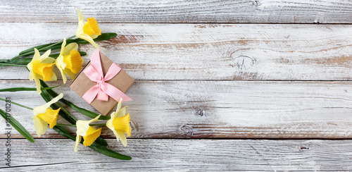 Yellow daffodils and gift box on white weathered wooden boards