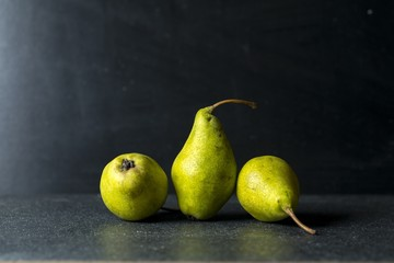 Green pears lying on dark background