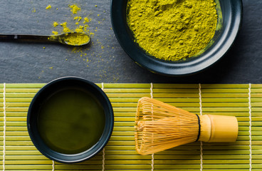 Flat lay of organic green tea powder (Matcha) in a bowl with bamboo whisk (Chasen)