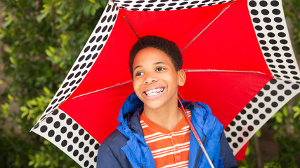 Happy African American boy laughing, holding umbrella