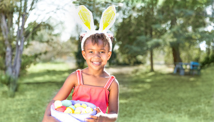 Cute African American girl wearing bunny ears, holding Easter basket with eggs.