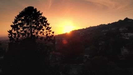 Fotobehang - Aerial view of sunset sun peaking over Hollywood Hills skyline, Los Angeles cityscape in background. 4K UHD.