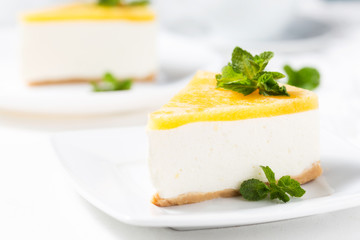 No-bake cheesecake decorated peach jelly and mint leaves on a white plate
