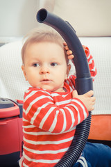 Little baby boy sitting at home and playing with pipe of vacuum cleaner