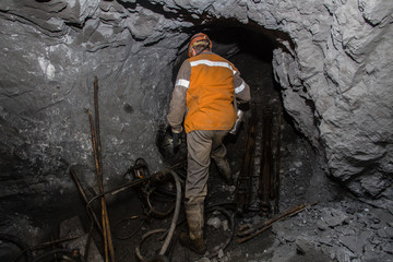 Underground iron ore mine shaft tunnel gallery with miners drilling