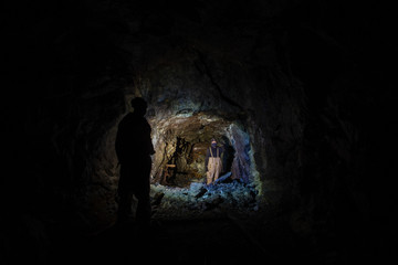 Underground abandoned gold ore mine shaft tunnel gallery with miners