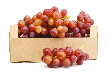 Red grapes isolated in wooden crate on white