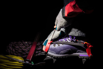 Close up of crampon and plastic boot for mountaineering. Hiking equipment on the glacier, illuminated by the light of a head lamp