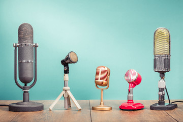 Retro old microphones for press conference or interview recording on wooden table front gradient aquamarine wall background. Vintage old style filtered photo