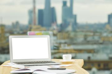 Creative desktop with empty white laptop