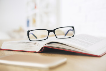 Glasses, book and smartphone