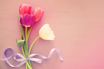 bouquet of pink and white tulips over pastel wooden background. Top view.