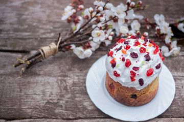 Easter cake garnished with dried cherries and cranberries stands on a wooden table, lies near a bouquet of blooming apricots.Space for text.