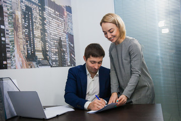 Female personal assistant gives papers for sign to boss businessman. Business routine at office