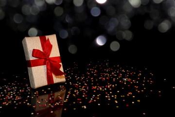 красивый подарок с красной лентой на черном фоне с разноцветным конфетти