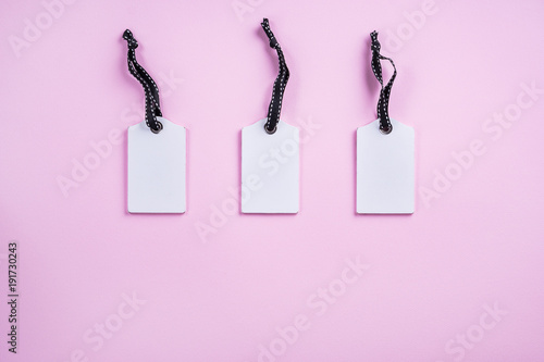 empty white tags in a row on pink background top view mock up