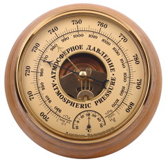 Old yellow-brown aneroid barometer in wooden body on a white