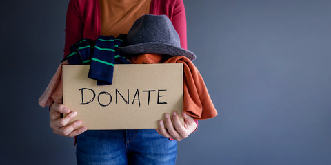 Donation Concept. Woman holding a Donate Box with full of Clothes. standing by the Wall in House