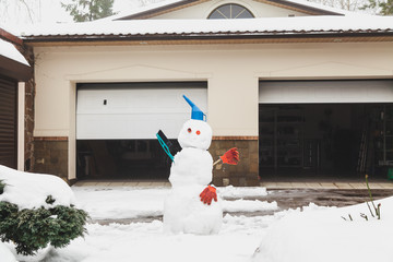 funny snowman stands in front of  garage