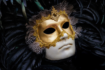 Detailed close-up photo of a gold and white venetian style renaissance mask with shiny black featheres