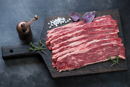 Raw fresh marbled beef bacon on a black wooden chopping board, studio shot