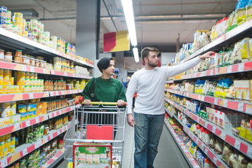 A young beautiful couple walking with a supermarket cart and choosing products. Family shopping at a supermarket