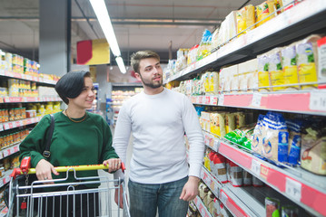 A positive, beautiful young couple chooses to eat a supermarket. Look at the shelf with the products. Family shopping at a supermarket