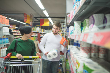 A young couple with a basket buys household goods for a home in a supermarket. Family shopping at the store