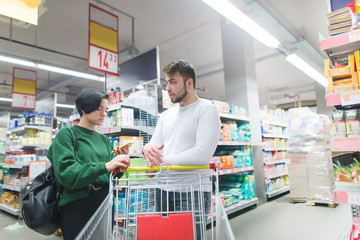 A young couple is standing in the middle of a supermarket. The girl is looking at the list of goods in her emoticon