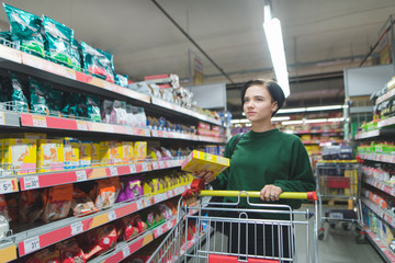 Portrait of a buyer girl with packaging in the middle of a supermarket. A beautiful and positive girl shopping in a supermarket