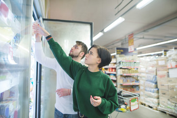 The couple takes frozen foods from the supermarket refrigerator. Family shopping at a supermarket
