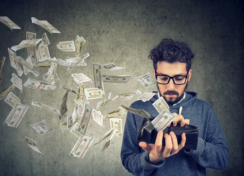 Hipster man looking at his wallet with money dollar banknotes flying out away