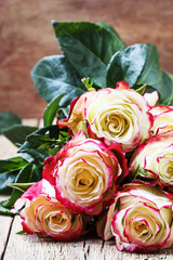 Festive bouquet of red and white roses, Valentines Day card, vintage wooden background, selective focus