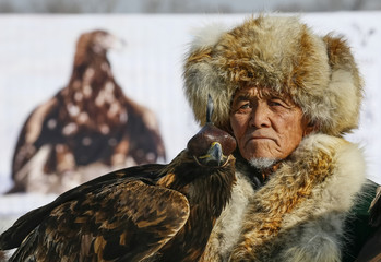 An elderly hunter with his tamed golden eagle attends a closing ceremony of an annual hunters competition at Almaty hippodrome