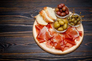 Meat plate of Italian prosciutto crudo or spanish jamon on wooden cutting board