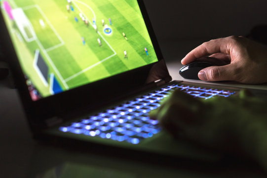 Young man playing soccer or football game online with laptop in dark or late at night. Competitive video gaming, electronic sports and esports concept.