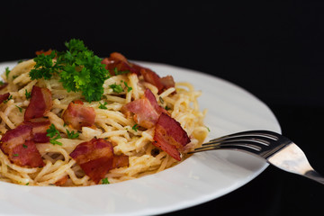 Spaghetti carbonara with bacon and cheese on white plate sprinkle with chopped parsley in close up view with copy space. Italian traditional homemade food for lunch or dinner so creamy and delicious.