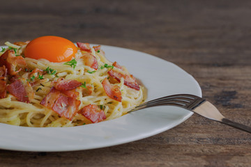 Spaghetti carbonara with bacon, cheese, yolk and sprinkle chopped parsley on wood table in side view with copy space. Italian traditional homemade food for lunch or dinner so creamy and delicious.