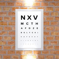 Tabella di misurazione della vista. Quadro appeso ad un muro di mattoni. Esame della vista. Lettere in stampatello