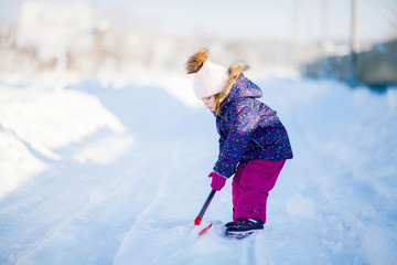 Little girl with a snow shovel.