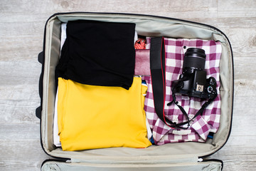Open traveler's bag with clothing and photo camera. Travel and vacations concept.
