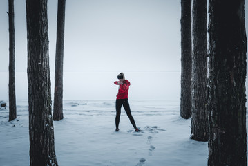 Athletic fit Caucasian warming up before workout in winter forest, standing near large lake