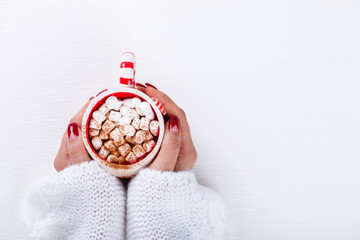 Female hands holding hot chocolate with marshmallow and cinnamon. Warming holiday drink on a white background.  Warm Christmas.CocoaTop view with Copy space